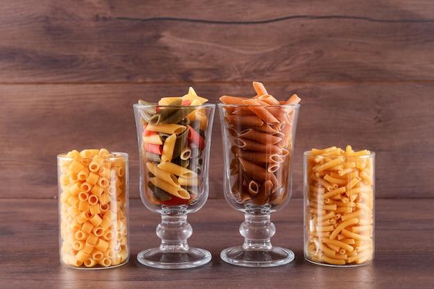 Pasta in glazen op houten oppervlak