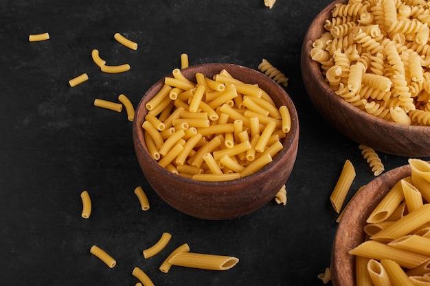 Pasta in houten bekers op zwarte ondergrond.