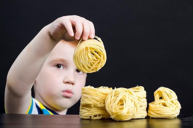 Pasta in rauwe gedroogde vorm in de handen van een kleine jongen, echte noedels en pasta, close-up in de keuken