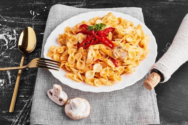 Pasta in tomatensaus in een wit bord met bestek opzij.