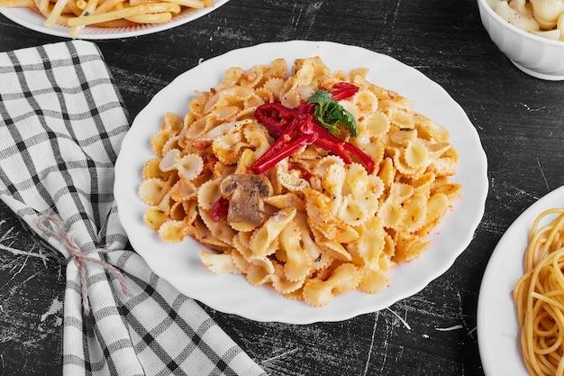 Pasta in tomatensaus in een witte plaat op zwarte achtergrond.