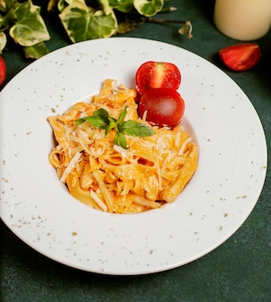 Pasta in tomatensaus met gehakte parmezaanse kaas, tomaat en basilicum.
