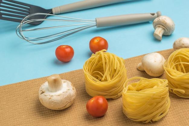 Pasta ingrediënten en kookgerei op de blauwe tafel. ingrediënten voor het maken van pasta.