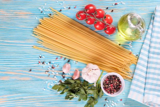 Pasta ingrediënten en kruiden op blauwe houten ondergrond. bovenaanzicht.