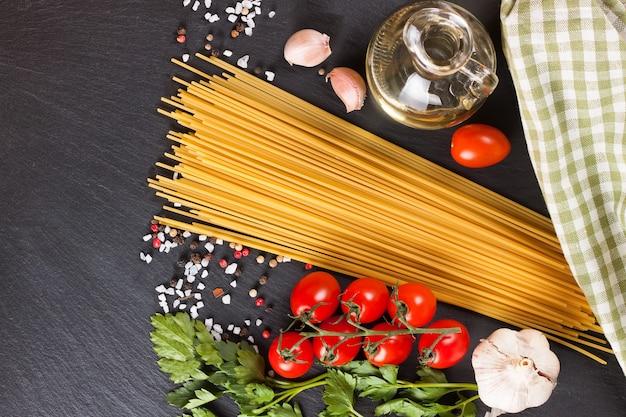 Pasta-ingrediënten en kruiden op zwarte leisteenoppervlak. bovenaanzicht, plat gelegd