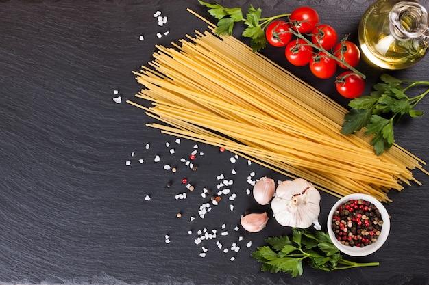 Pasta-ingrediënten en kruiden op zwarte leisteenoppervlak. bovenaanzicht, plat leggen met kopie ruimte.
