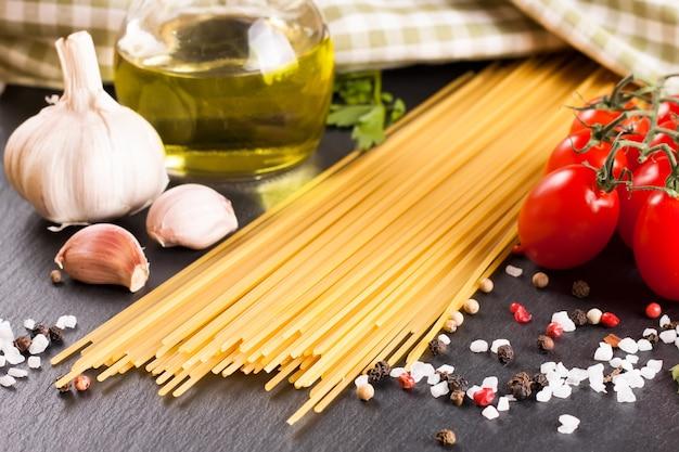 Pasta-ingrediënten en kruiden op zwarte leisteenoppervlak. bovenaanzicht.