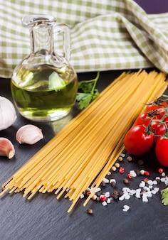 Pasta-ingrediënten en kruiden op zwarte leisteenoppervlak.