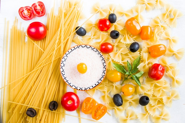 Pasta ingrediënten, rauwe pasta, kerstomaatjes, olijven, zout en basilicum bladeren op de witte achtergrond