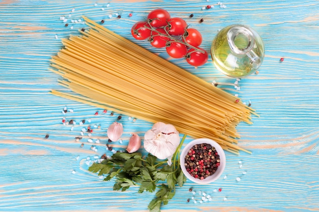 Pasta-ingridients en kruiden op blauwe houten oppervlak. bovenaanzicht, plat gelegd.