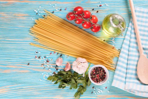 Pasta-ingridients en kruiden op blauwe houten oppervlak. bovenaanzicht.