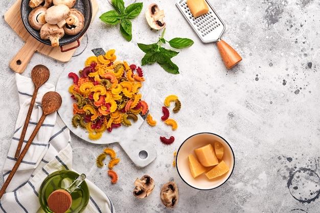 Pasta. italiaanse pasta. insalata di pasta en groenten koken ingrediënten, kaas, champignons en basilicum op oude stenen achtergrond. italiaans eten koken ingrediënten. bovenaanzicht met kopie ruimte.