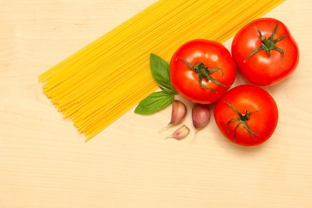 Pasta, knoflook, tomaten en basilicum op een houten bord. bovenaanzicht