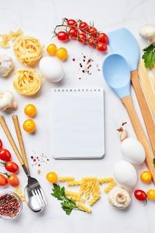 Pasta koken achtergrond met kladblok voor tekst, tomaten, kruiden, champignons, eieren verspreid over lichte marmeren achtergrond, bovenaanzicht. italiaanse keuken concept