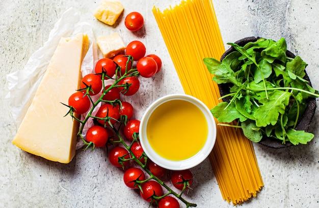 Pasta koken. grondstoffen voor het koken van pasta met tomatensaus en kaas op een grijze ondergrond.
