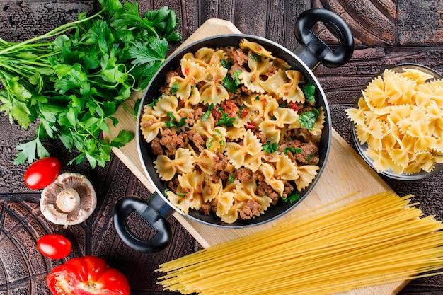 Pasta maaltijd in de pan met rauwe pasta, champignons, peterselie, tomaat