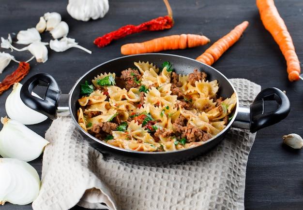 Pasta maaltijd in een pan met ui, knoflook, wortelen, paprika