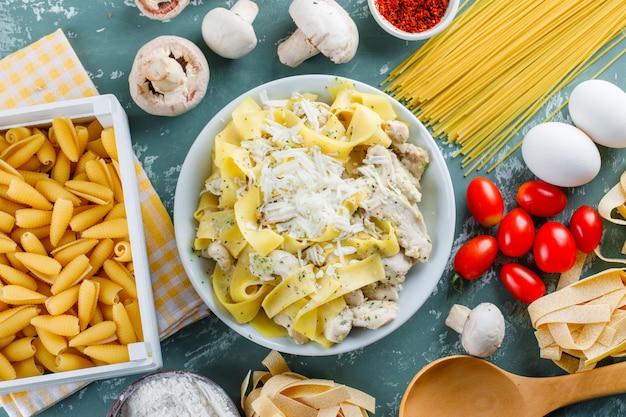 Pasta maaltijd in een plaat met rauwe pasta, tomaat, meel, champignons, eieren, lepel