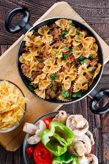 Pasta maaltijd in pan met rauwe pasta, champignons, paprika, tomaat