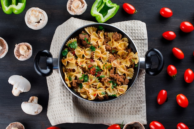 Pasta maaltijd met champignons, paprika, tomaten in een pan