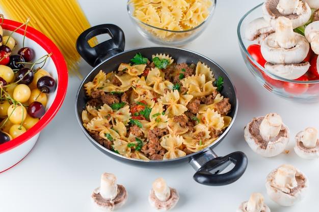 Pasta maaltijd met rauwe pasta, champignons, tomaat, kers in een pan