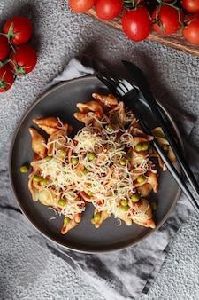 Pasta met cherrytomaatjes, erwten en parmezaanse kaas. huisgemaakte italiaanse pasta met tomaten en saus