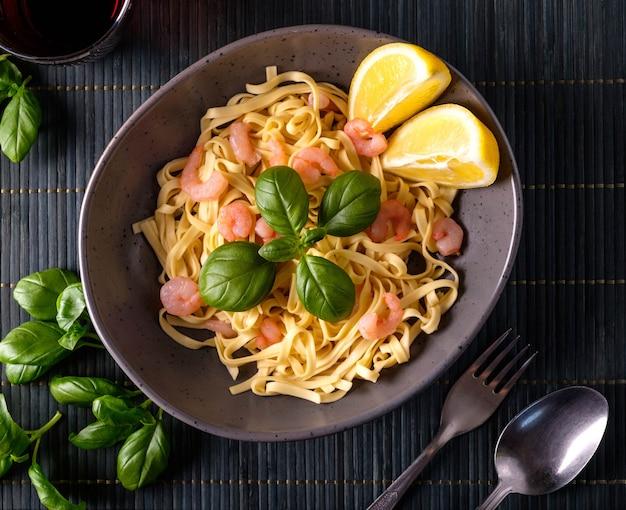 Pasta met garnalen, basilicum en tomaten op een donkere achtergrond