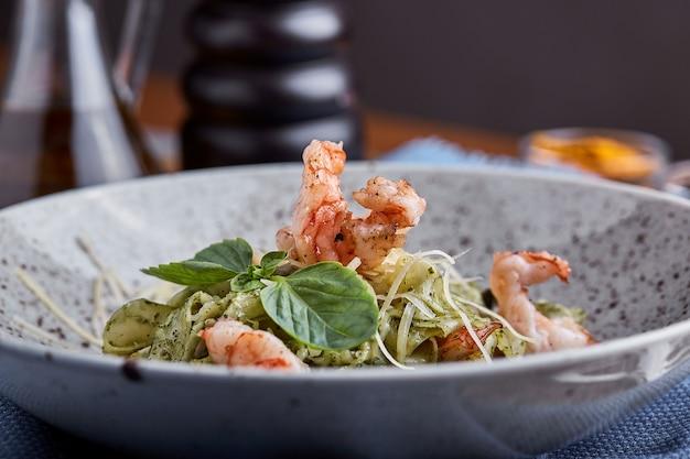 Pasta met garnalen en basilicum saus. italiaanse keuken. traditionele italiaanse pasta met garnalen en basilicum, olijfolie en pestosaus.