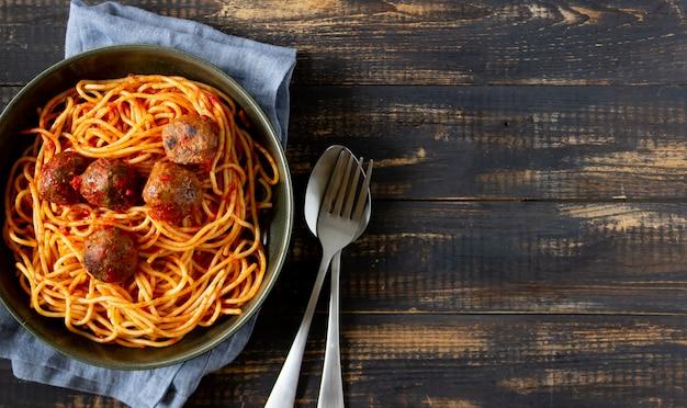 Pasta met gehaktballetjes en tomatensaus op een houten achtergrond.