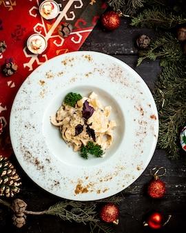 Pasta met kaas en champignons overgoten met basilicum