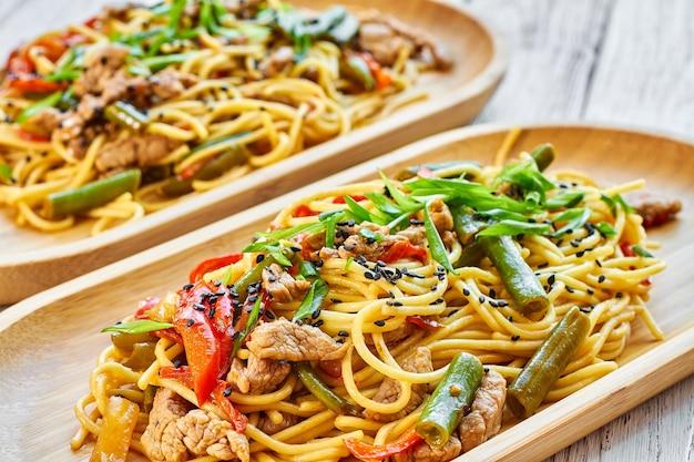 Pasta met kalfsvlees en groenten op een houten ondergrond in een bamboe bord