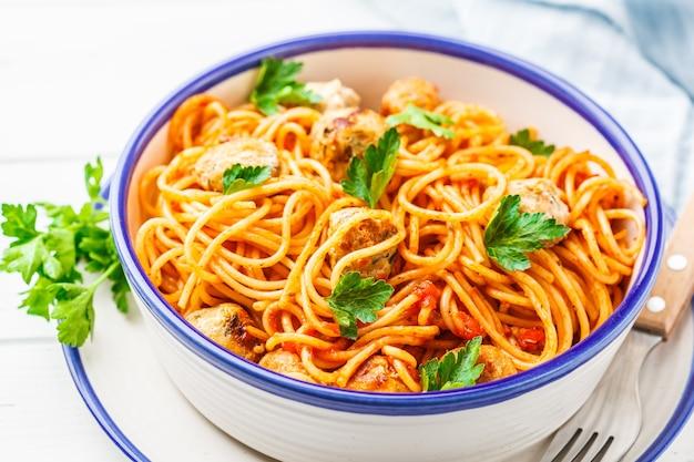 Pasta met kalkoengehaktballetjes en tomatensaus in een witte schotel