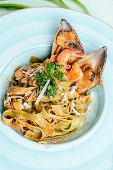Pasta met oesters gegarneerd met kruiden en kaas