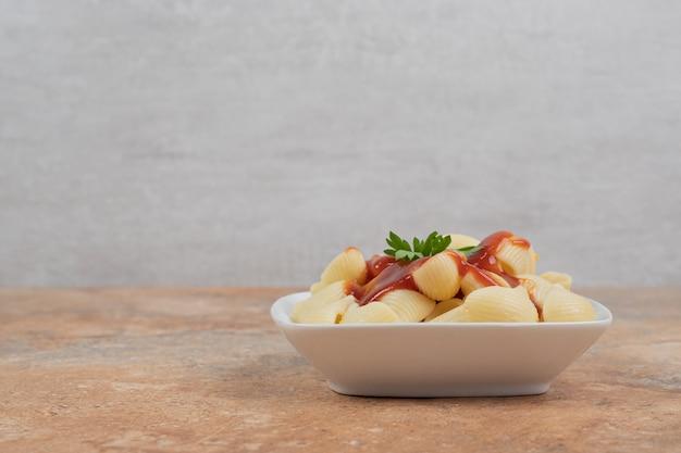 Pasta met peterselie en tomatensaus in witte kom