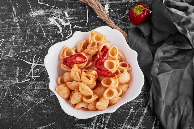 Pasta met rode chili in een keramische kom, bovenaanzicht.