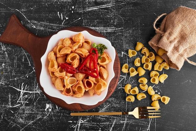 Pasta met rode chili peper in een witte kom.