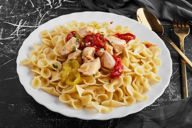 Pasta met rode pepers in een witte plaat.
