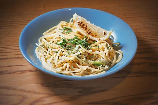 Pasta met romige saus in blauw bord en cocktail op tafel