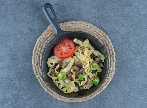 Pasta met rundvlees delen op zwarte pan.