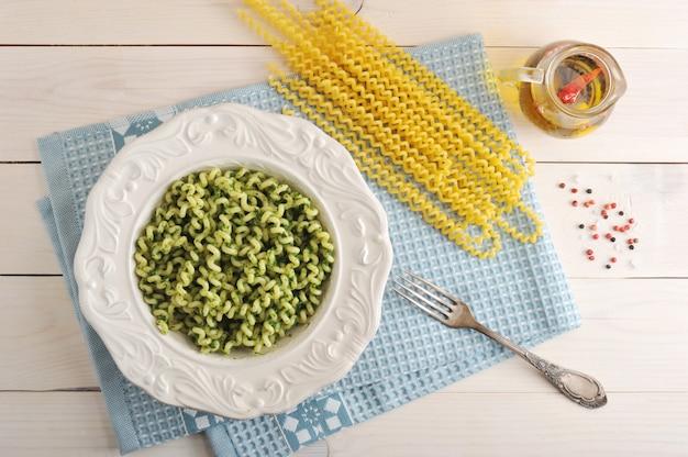 Pasta met spinazie in een schotel en ingrediënten voor het koken van pasta
