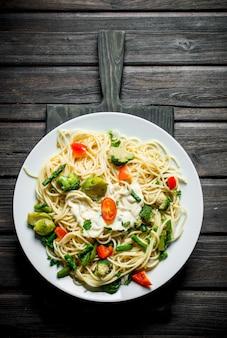 Pasta met spruitjes, broccoli en tomaten. op zwarte houten achtergrond