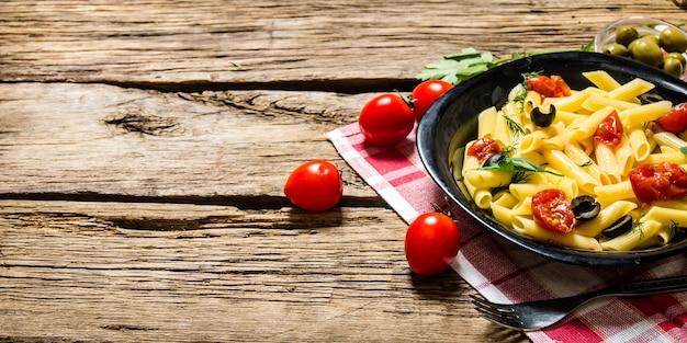 Pasta met tomaten, olijven en kruiden op een houten tafel