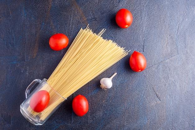 Pasta met tomaten op donkere achtergrond