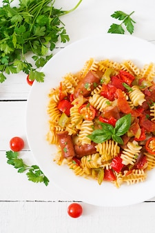 Pasta met tomatensaus met worst, tomaten, groene basilicum ingericht in witte plaat op een houten tafel.