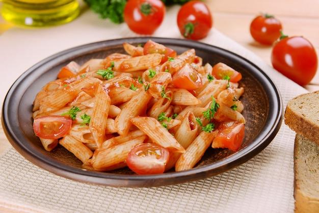Pasta met tomatensaus op plaat op tafel close-up