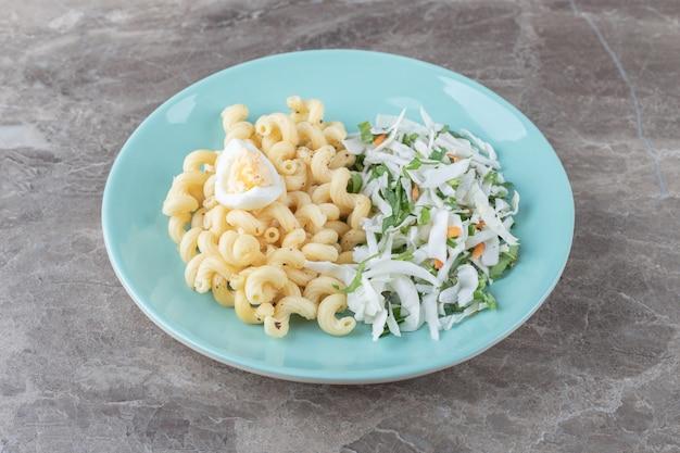 Pasta met verse salade en ei op blauw bord.
