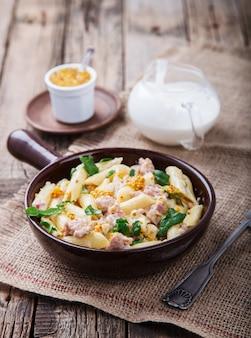 Pasta met vlees, kruiden en room met een saus
