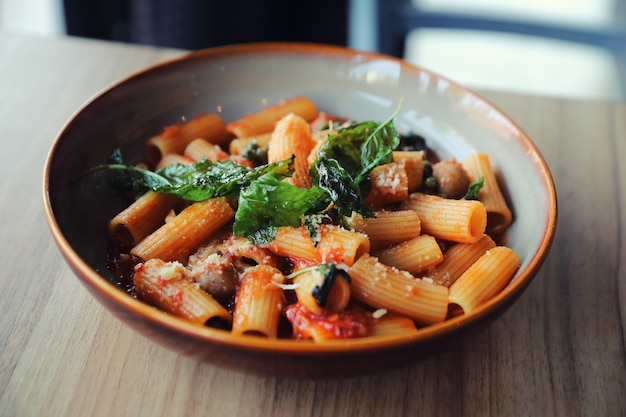 Pasta met worst in tomatensaus op houten tafel