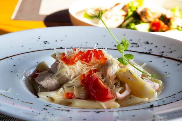Pasta met zalm en rode kaviaar, delicatessen, zeevruchten in het restaurant