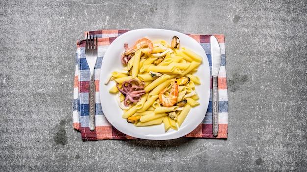 Pasta met zeevruchten op een plaat op de stof op de stenen tafel